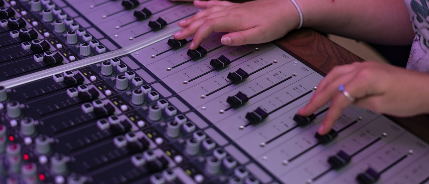 hands at a mixing desk