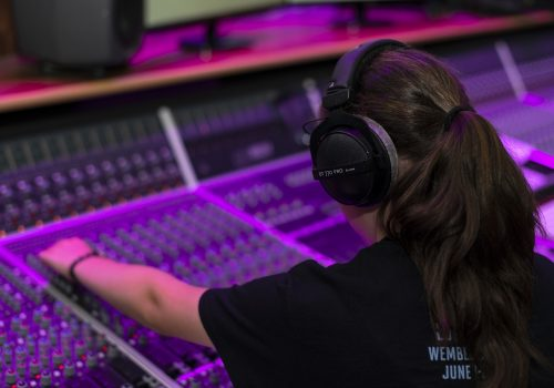 Young woman wearing headphones and using a mixing desk